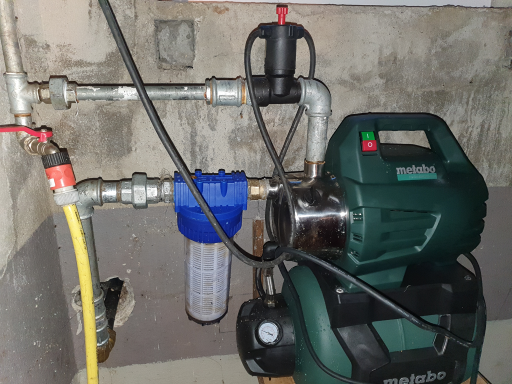 A house water system mounted in a basement with two pipes connected.